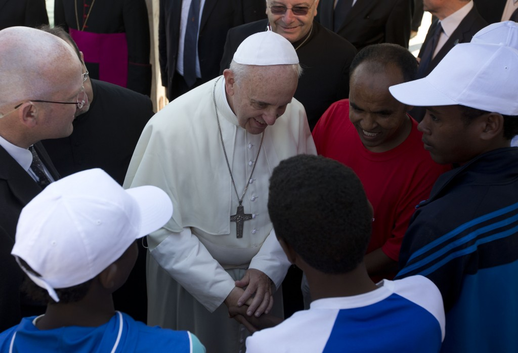 FILE - In this July 8, 2013 file photo, Pope Francis speaks to migrants, some wearing white caps, during his visit to the island of Lampedusa, souther...
