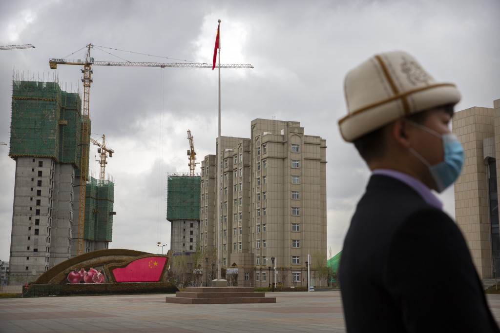 A man wearing a Kyrgyz hat stands on a plaza near a display with the Chinese flag at the Xinjiang Islamic Institute, as seen during a government organ...