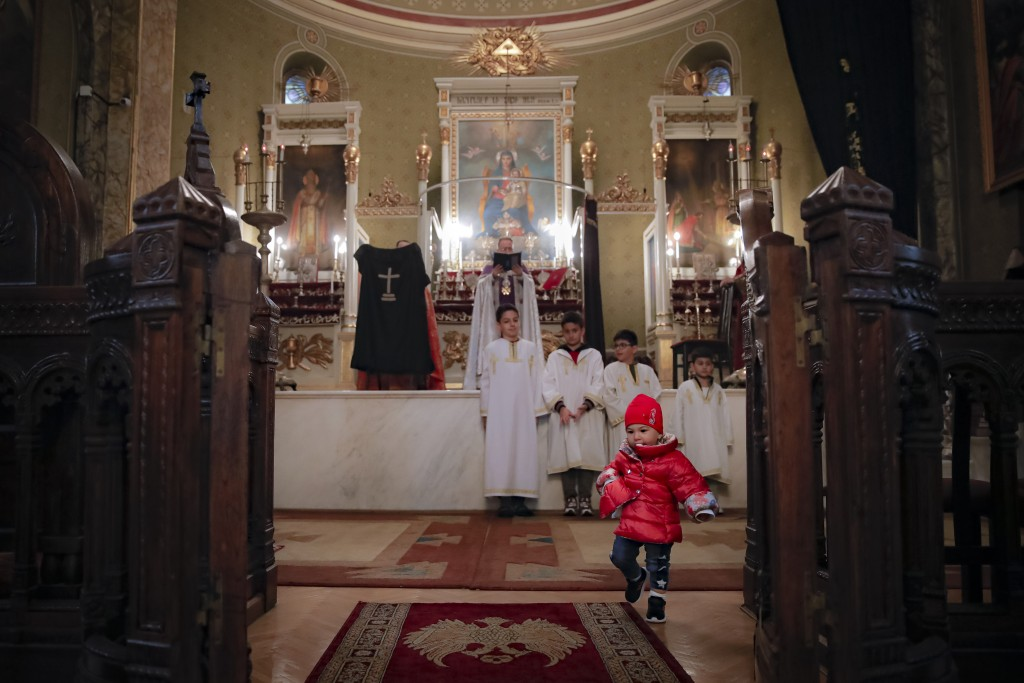 A baby wanders around while Iraq-born Archbishop Datev Hagopian, center, leads a Maundy Thursday religious service, that included the symbolic washing...