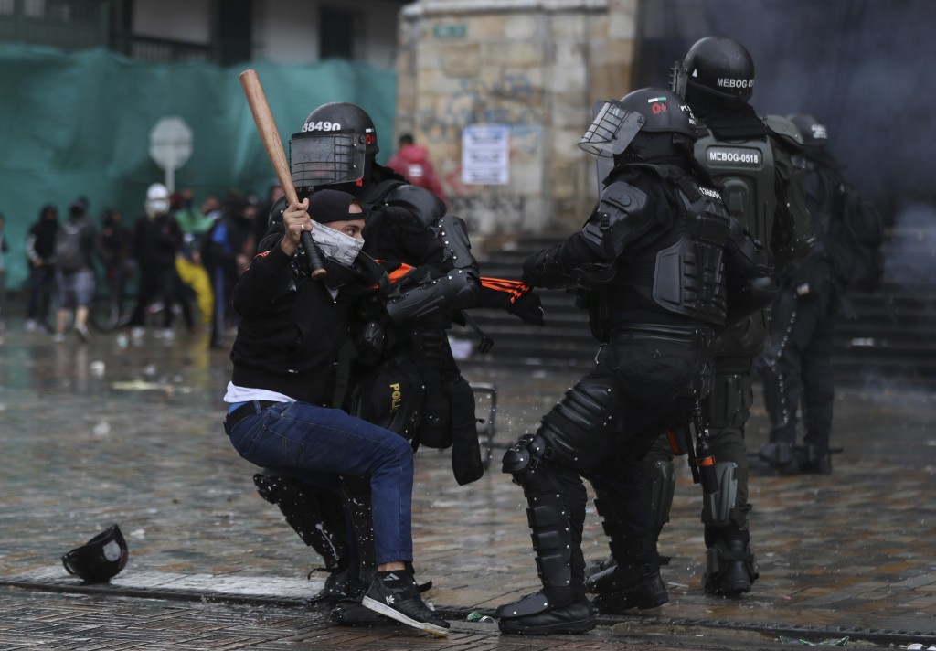 A protester clashes with the police during an anti-government protest in Bogota, Colombia, Wednesday, May 5, 2021. The protests that began last week o...