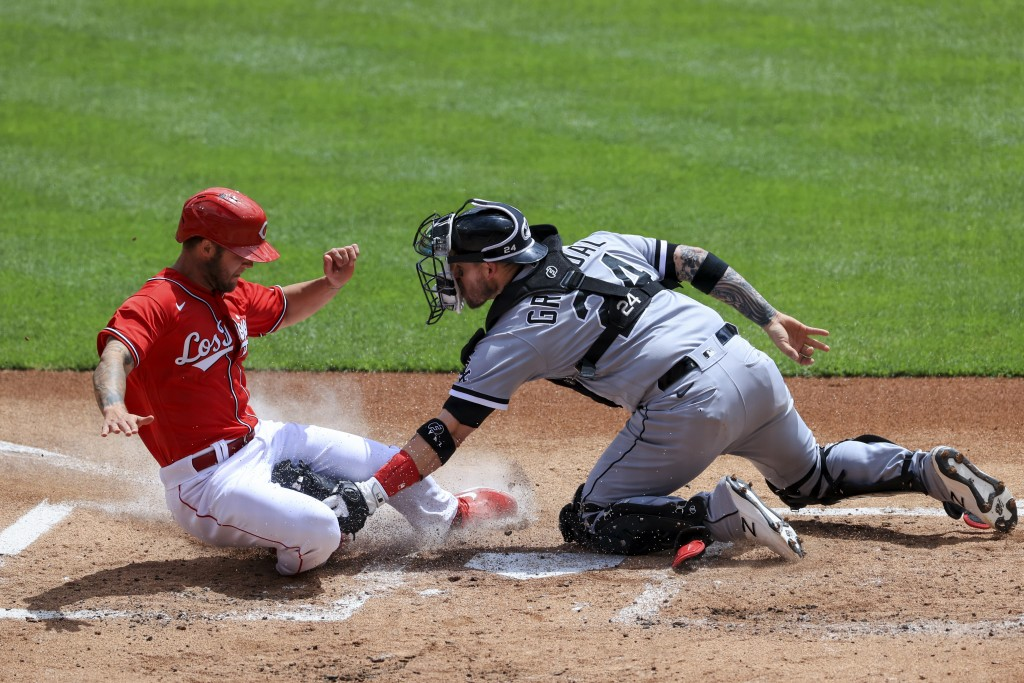 Cincinnati Reds' Nick Senzel, left, is tagged out at home plate by Chicago White Sox Yasmani Grandal during the first inning of a baseball game in Cin...