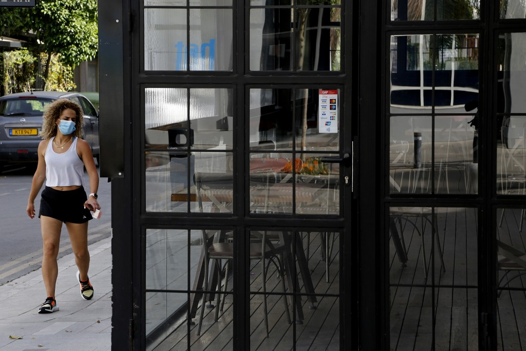 A woman wearing protective face mask walks outside of a closed cafe amid COVID-19 pandemic restrictions government in central capital Nicosia, Cyprus,...