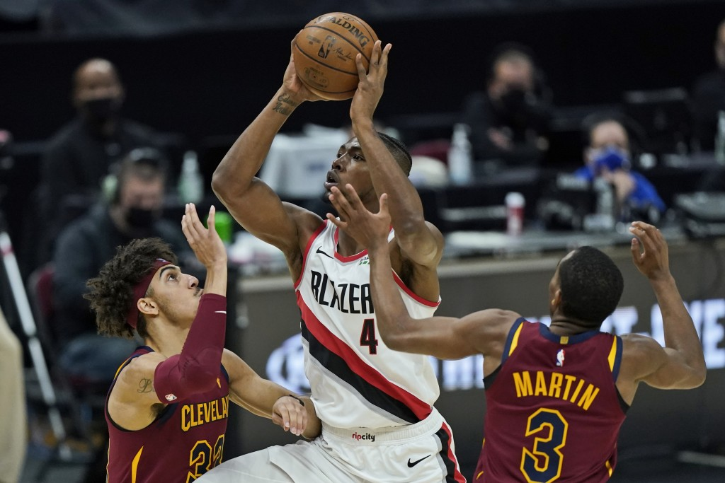 Portland Trail Blazers' Harry Giles III (4) drives to the basket against Cleveland Cavaliers' Brodric Thomas (33) and Jeremiah Martin (3) during the s...