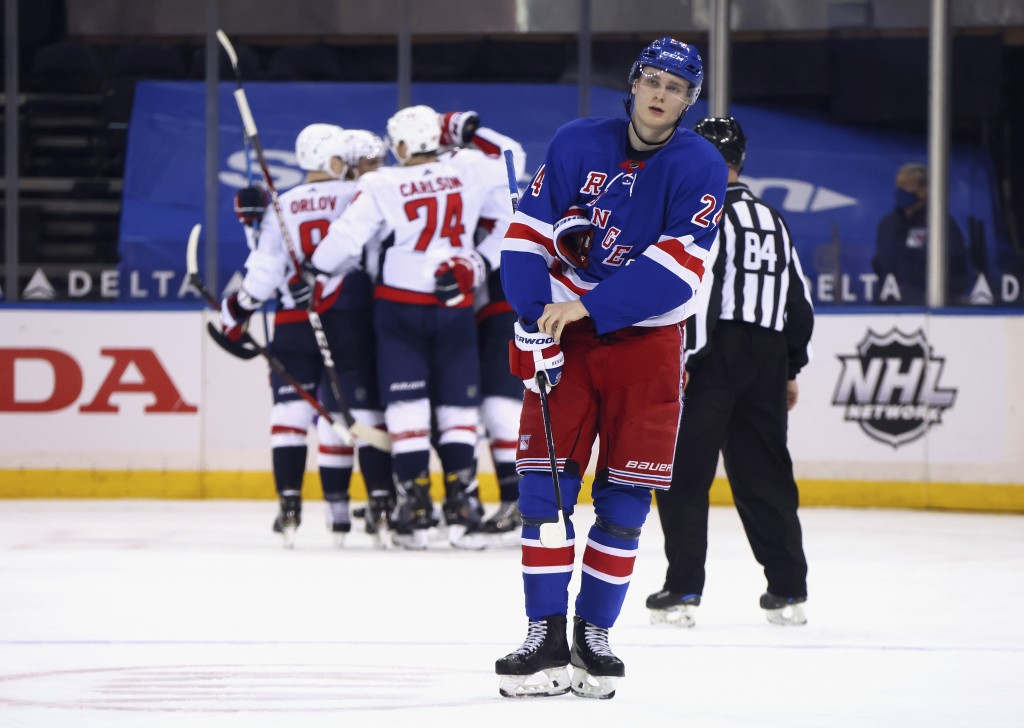 New York Rangers' Kaapo Kakko (24) skates back to the bench as the Washington Capitals celebrate a second-period goal by Nic Dowd during an NHL hockey...