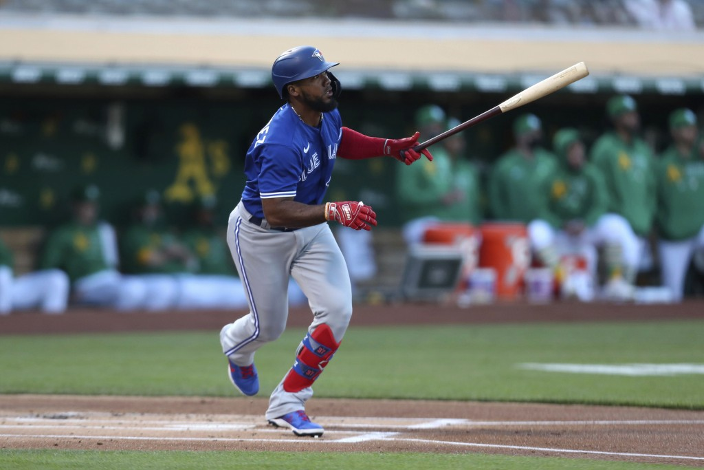 Toronto Blue Jays' Teoscar Hernandez watches his RBI single against the Oakland Athletics during the first inning of a baseball game in Oakland, Calif...