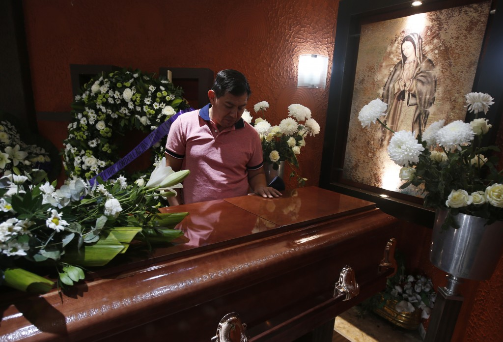 Jesus Sanchez places his hand on the casket containing the remains of his wife Liliana Lopez, 37, who died in the Mexico City Metro collapse disaster,...