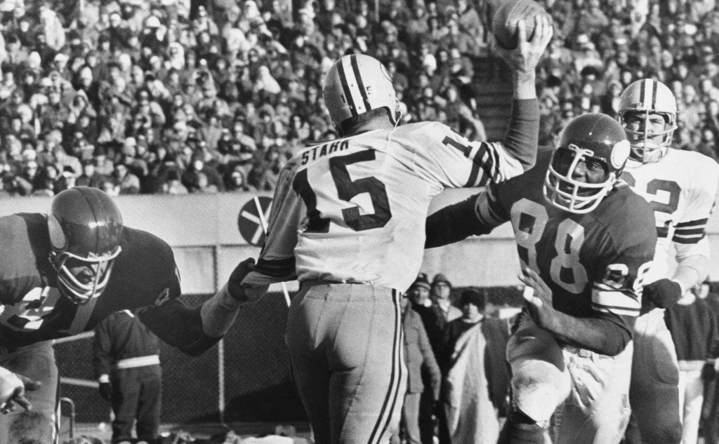 File-This Nov. 23, 1970 file photo shows Green Bay Packers quarterback Bart Starr (15) looking for a receiver as Minnesota Vikings Alan Page (88) char...