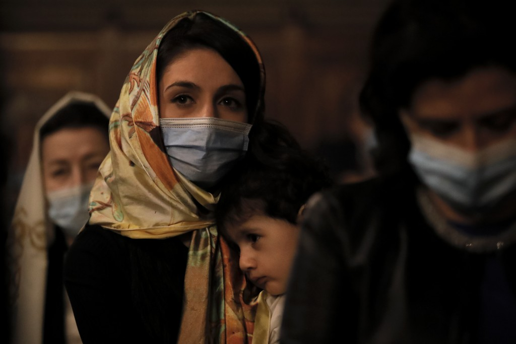 A woman of the Armenian community in Romania, wearing face mask, holds a young child during the Easter religious service, at the Armenian Church in Bu...