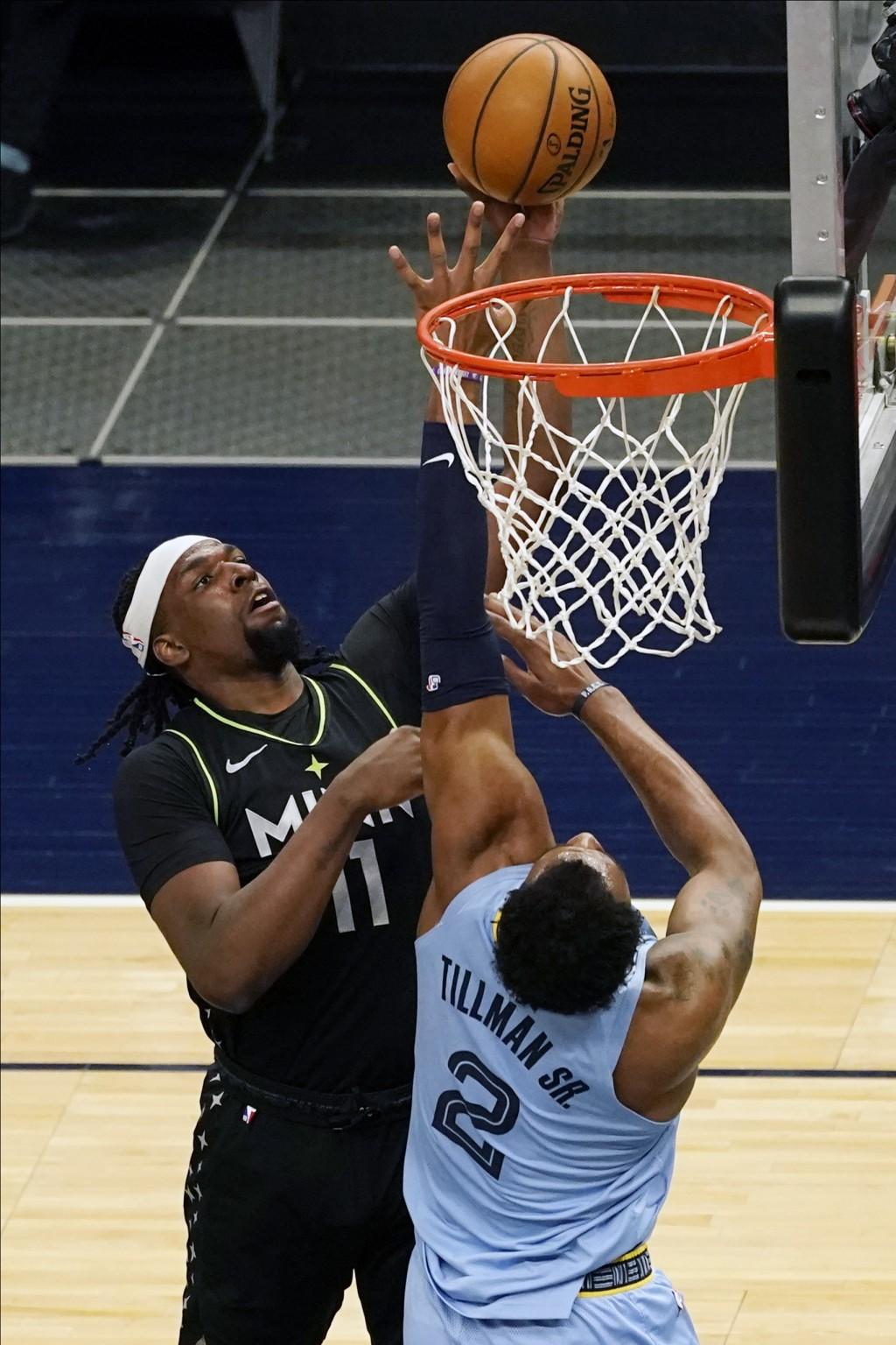 Minnesota Timberwolves' Naz Reid (11) shoots as Memphis Grizzlies' Xavier Tillman defends during the first half of an NBA basketball game Wednesday, M...