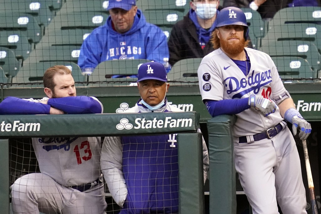 Los Angeles Dodgers' Max Muncy, left, manager Dave Roberts, center, and Justin Turner watches during the third inning of a baseball game against the C...
