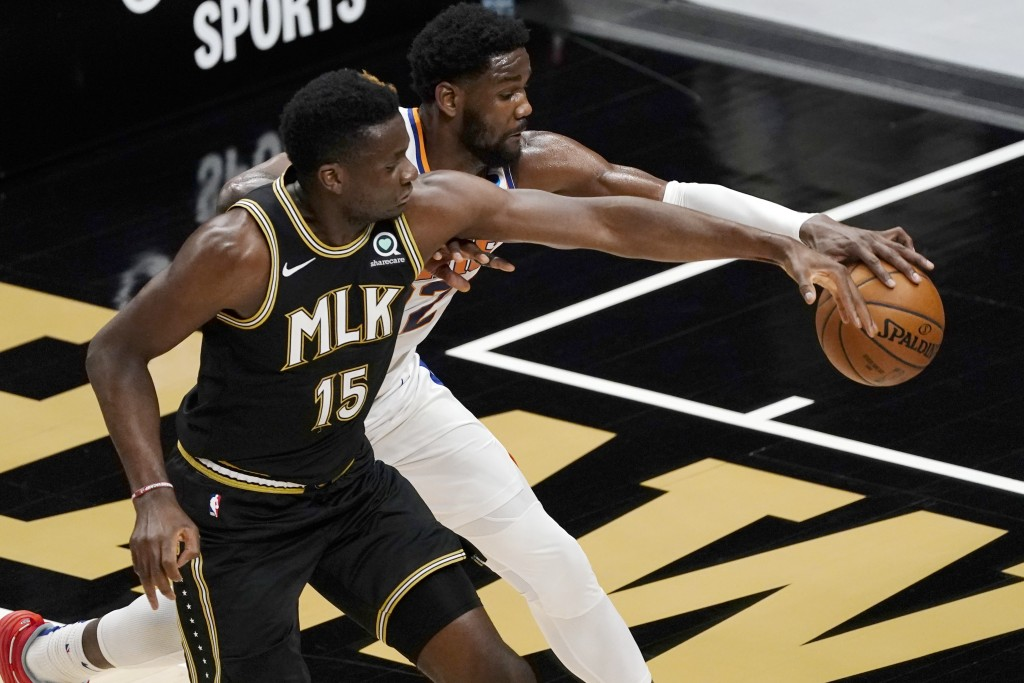 Phoenix Suns center Deandre Ayton (22) and Atlanta Hawks center Clint Capela (15) fight for a loose ball in the first half of an NBA basketball game W...