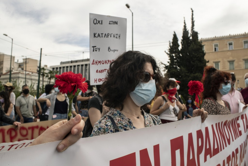 Members of the communist party-affiliated PAME wearing protective face masks hold red carnations, as they protest during a rally commemorating May Day...