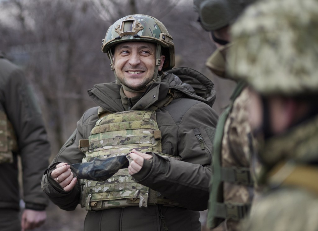 FILE - In this Thursday, Feb. 11, 2021 file photo, Ukrainian President Volodymyr Zelenskyy talks with servicemen as he visits the war-hit Donetsk regi...