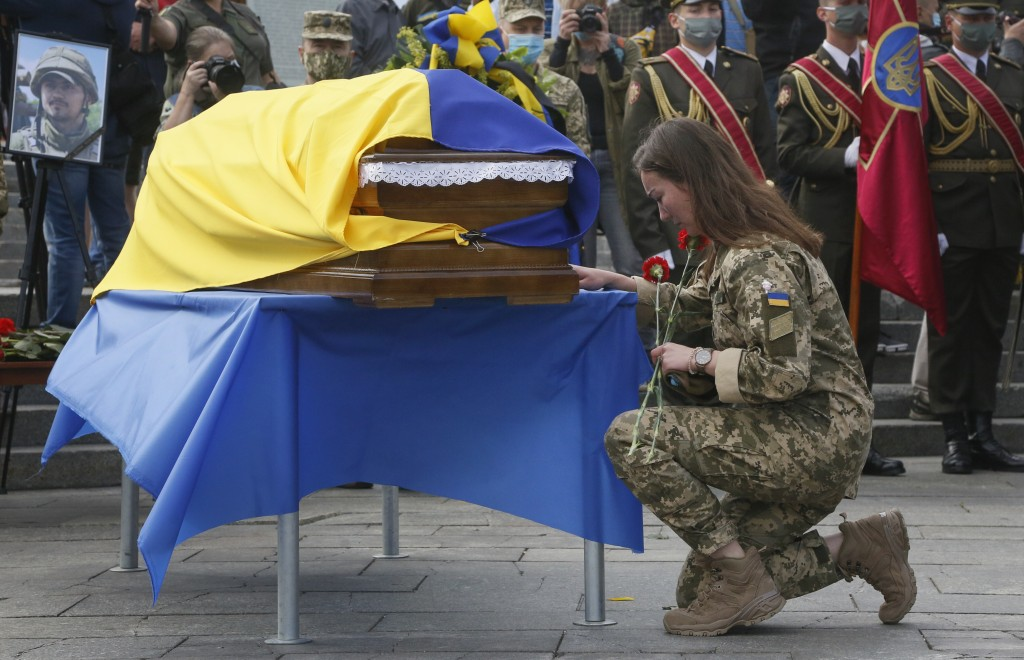 FILE - In this July 14, 2020 file photo, a Ukrainian soldier kneels at the coffin of serviceman Taras Matviiv, honored with the Hero of Ukraine highes...