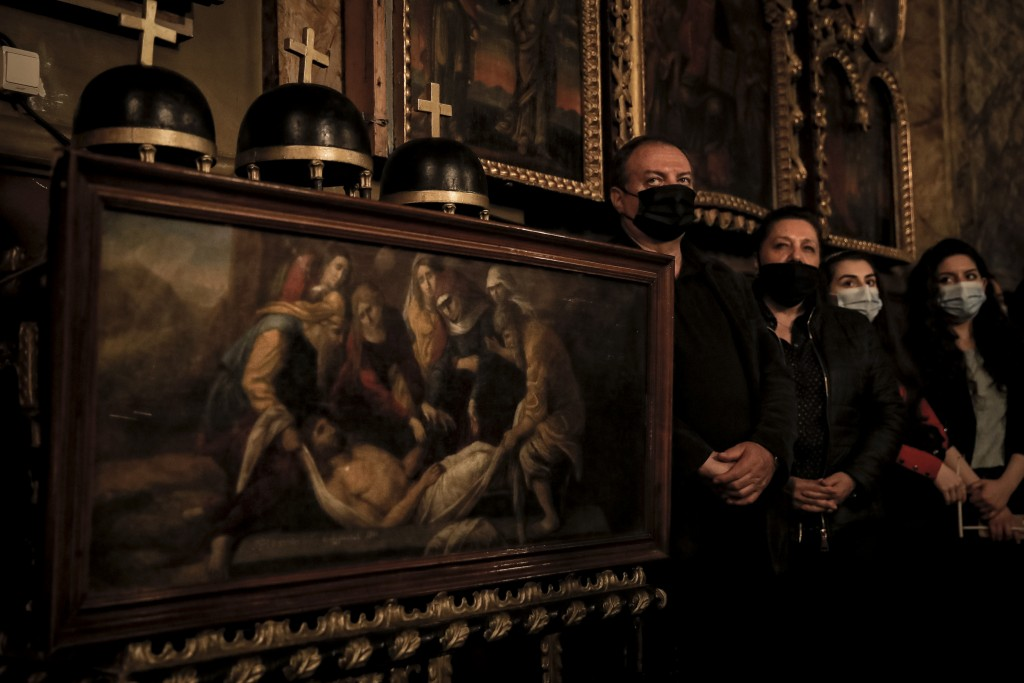 Members of the Armenian community in Romania, wearing face masks, stand during the Easter religious service, at the Armenian Church in Bucharest, Roma...