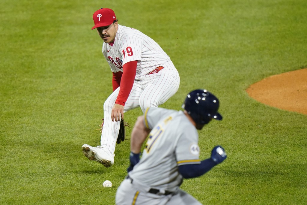 Philadelphia Phillies pitcher JoJo Romero, left, fields a ground out by Milwaukee Brewers' Travis Shaw during the fifth inning of baseball game, Wedne...