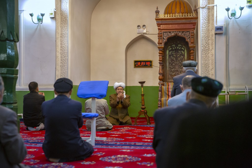 Uyghurs and other members of the faithful pray during services at the Id Kah Mosque in Kashgar in western China's Xinjiang Uyghur Autonomous Region, a...