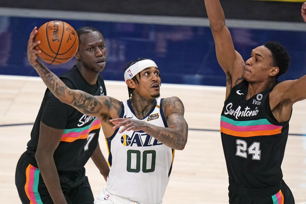 Utah Jazz guard Jordan Clarkson (00) goes to the basket as San Antonio Spurs guard Devin Vassell (24) defends during the second half of an NBA basketb...