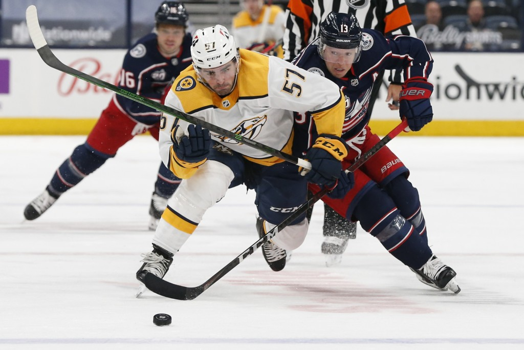 Nashville Predators' Dante Fabbro, left, and Columbus Blue Jackets' Cam Atkinson chase the puck during the second period of an NHL hockey game Wednesd...