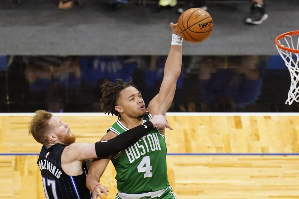 Orlando Magic forward Ignas Brazdeikis, left, fouls Boston Celtics guard Carsen Edwards (4) as he goes up for a shot during the second half of an NBA ...