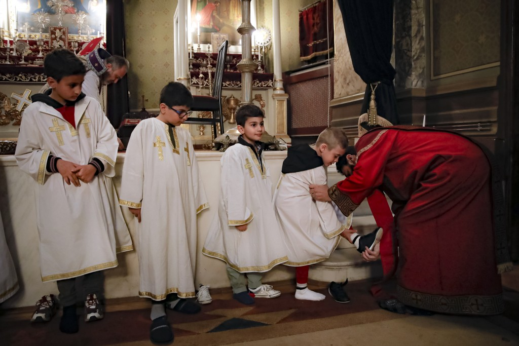 An Armenian clergyman helps a child remove his shoes before the washing of the feet ritual during a Maundy Thursday religious service, at the Armenian...