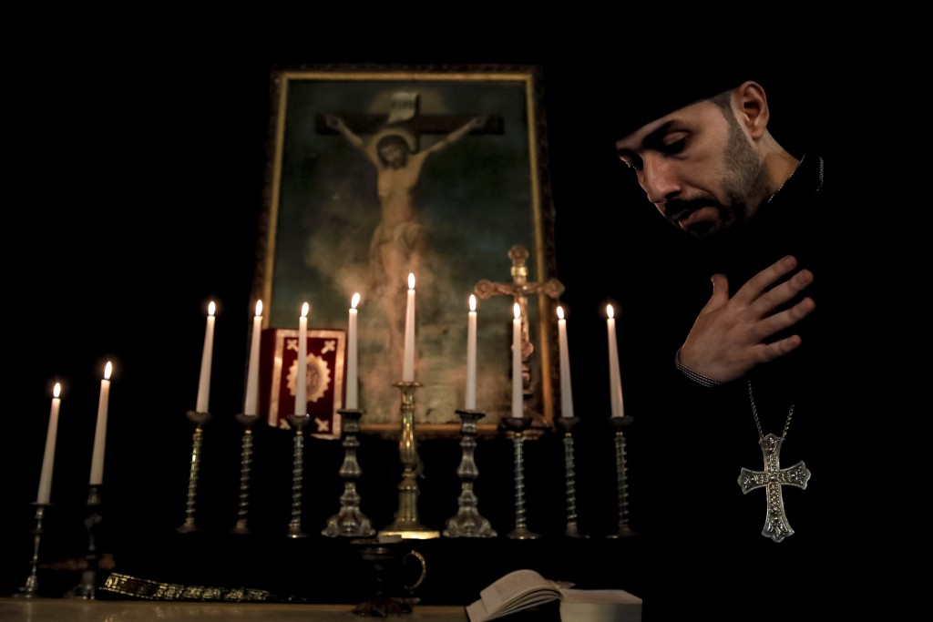 An Armenian clergyman walks by an icon depicting the crucifixion of Jesus Christ during a Maundy Thursday religious service, at the Armenian Church in...