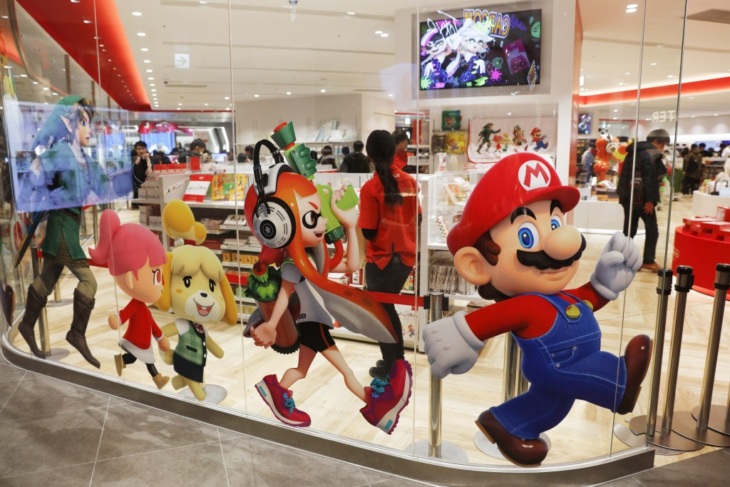 FILE - In this Jan. 23, 2020, file photo, Nintendo characters, including Mario, right, are seen on a glass of its official store in Tokyo. Nintendo Co...
