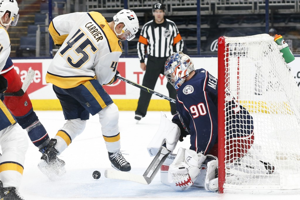Columbus Blue Jackets' Elvis Merzlikins, right, makes a save against Nashville Predators' Alexandre Carrier during the third period of an NHL hockey g...