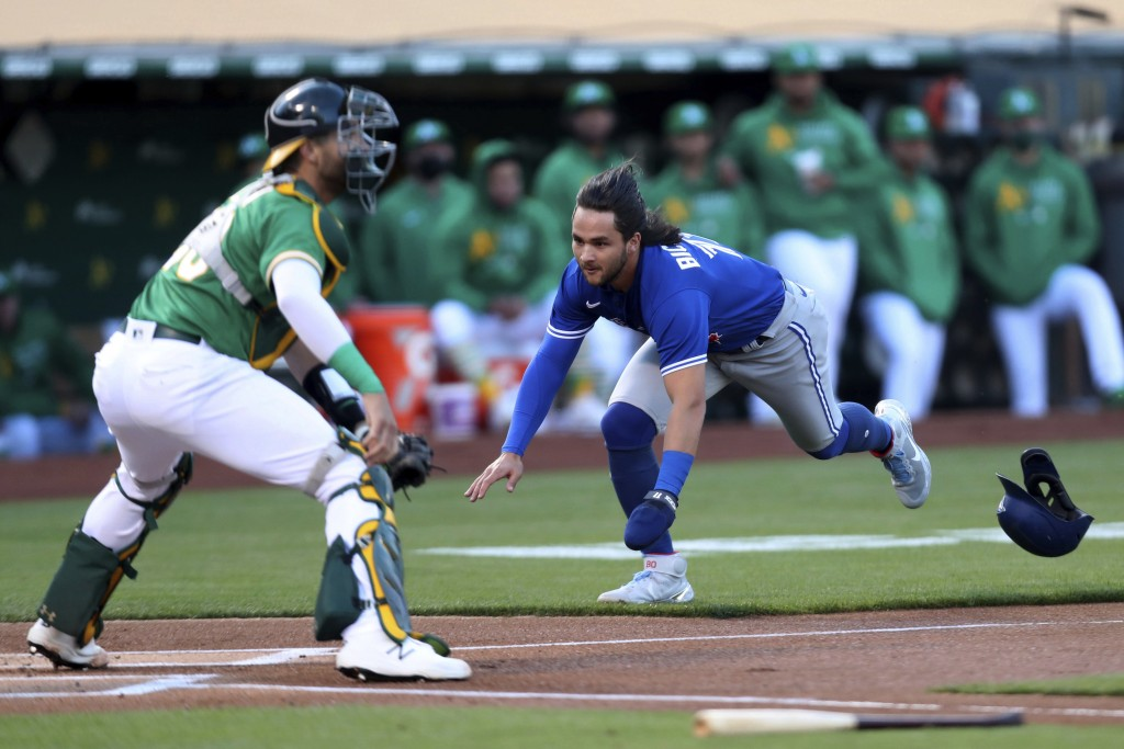 Toronto Blue Jays' Bo Bichette dives for home as Oakland Athletics' Austin Allen waits for the throw during the first inning of a baseball game in Oak...