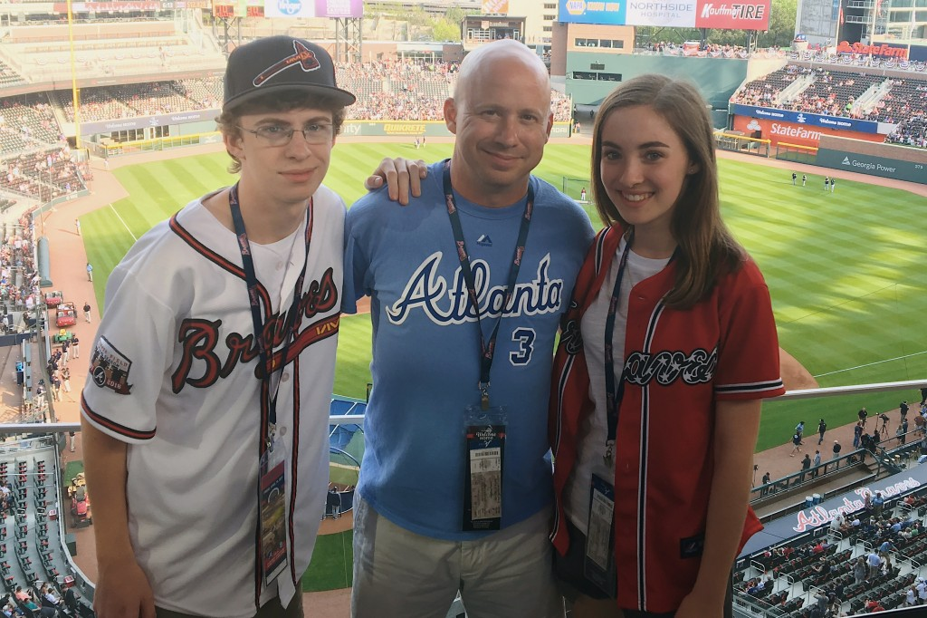 This photo provided by Bailie Brown shows Bailie Brown posed with her brother, Corbin, left, and father, Ken Brown, center, at an Atlanta Braves baseb...