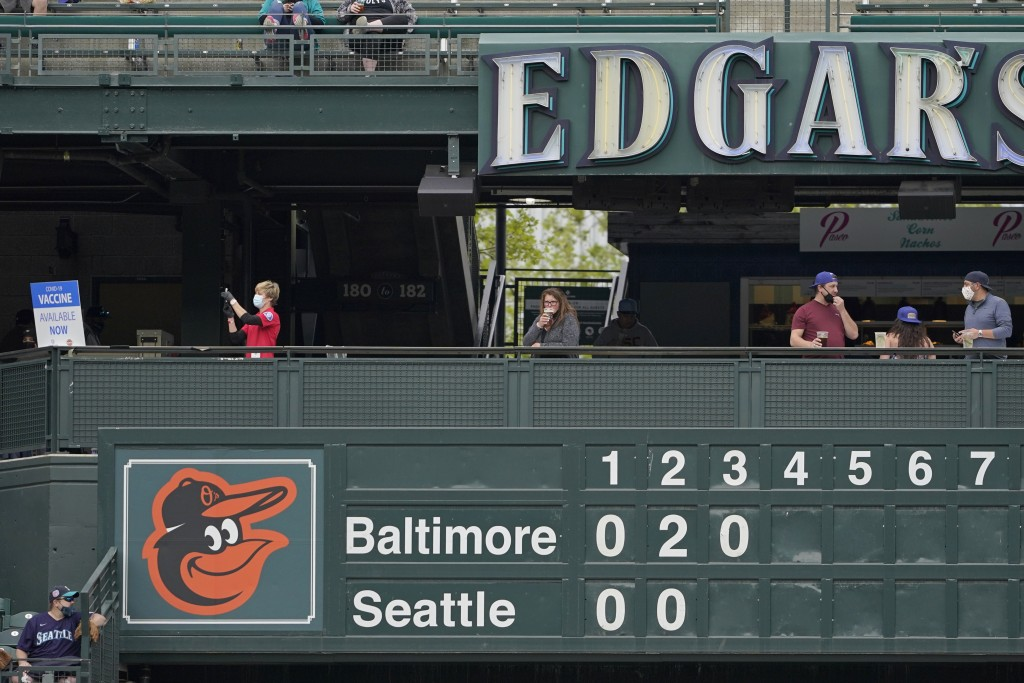 A Seattle Fire Dept. EMT, left, fills a syringe at a clinic administering free COVID-19 vaccines located above the manual scoreboard at T-Mobile Park ...