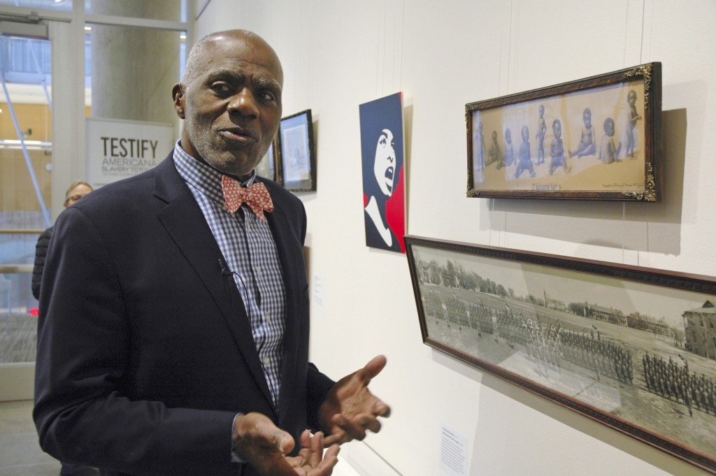 FILE - In this Jan. 11, 2018 photo, Alan Page, NFL Hall of Famer and retired Minnesota Supreme Court justice, stands in Minneapolis, by a photo of bla...