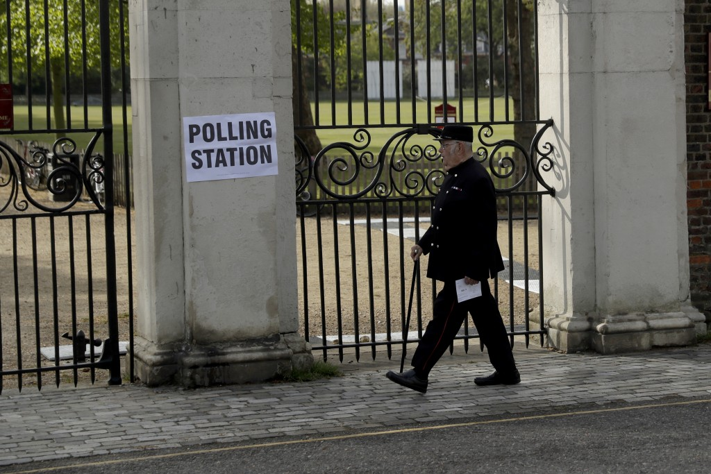 A Chelsea Pensioner walks past a sign for a polling station as he arrives to vote in London, Thursday, May 6, 2021. Millions of people across Britain ...