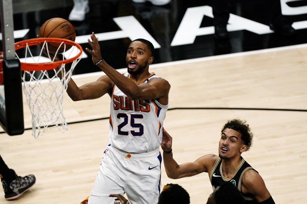 Phoenix Suns forward Deandre Ayton (25) scores as Atlanta Hawks guard Trae Young (11) defends in the first half of an NBA basketball game Wednesday, M...