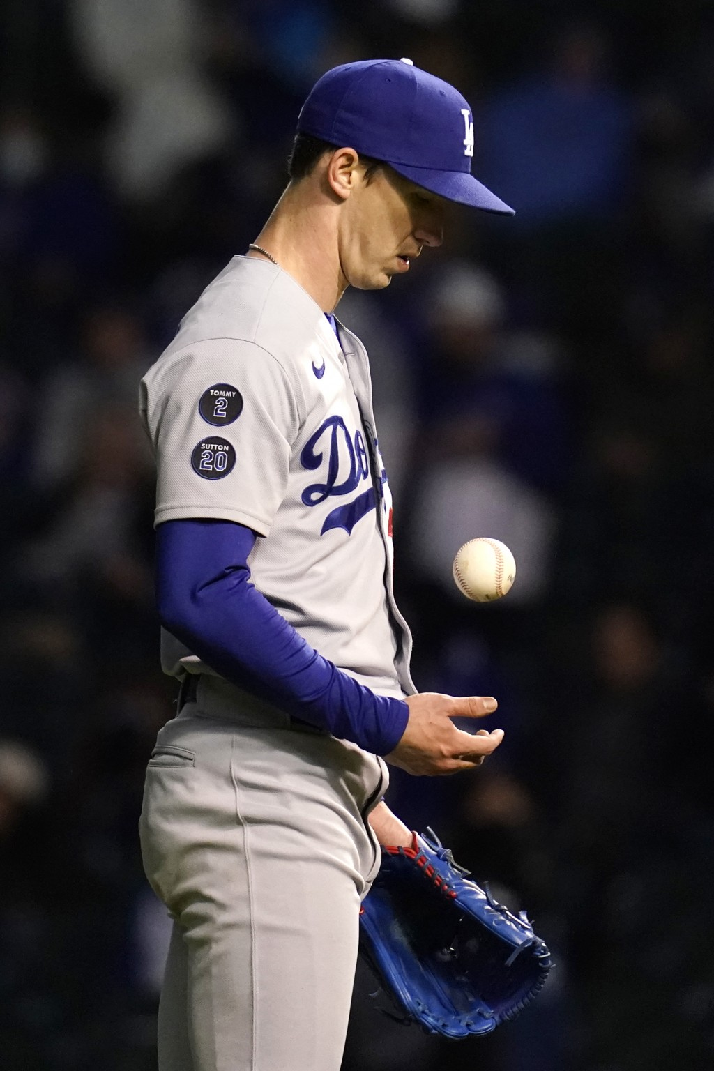 Los Angeles Dodgers starting pitcher Walker Buehler tosses the ball after Chicago Cubs' Jake Marisnick hit a two-run home run during the fifth inning ...