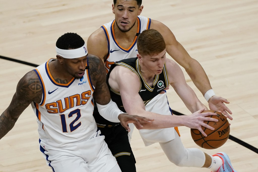 Atlanta Hawks guard Kevin Huerter (3) tries to go between Phoenix Suns Torrey Craig (12) and Devin Booker (1) in the first half of an NBA basketball g...