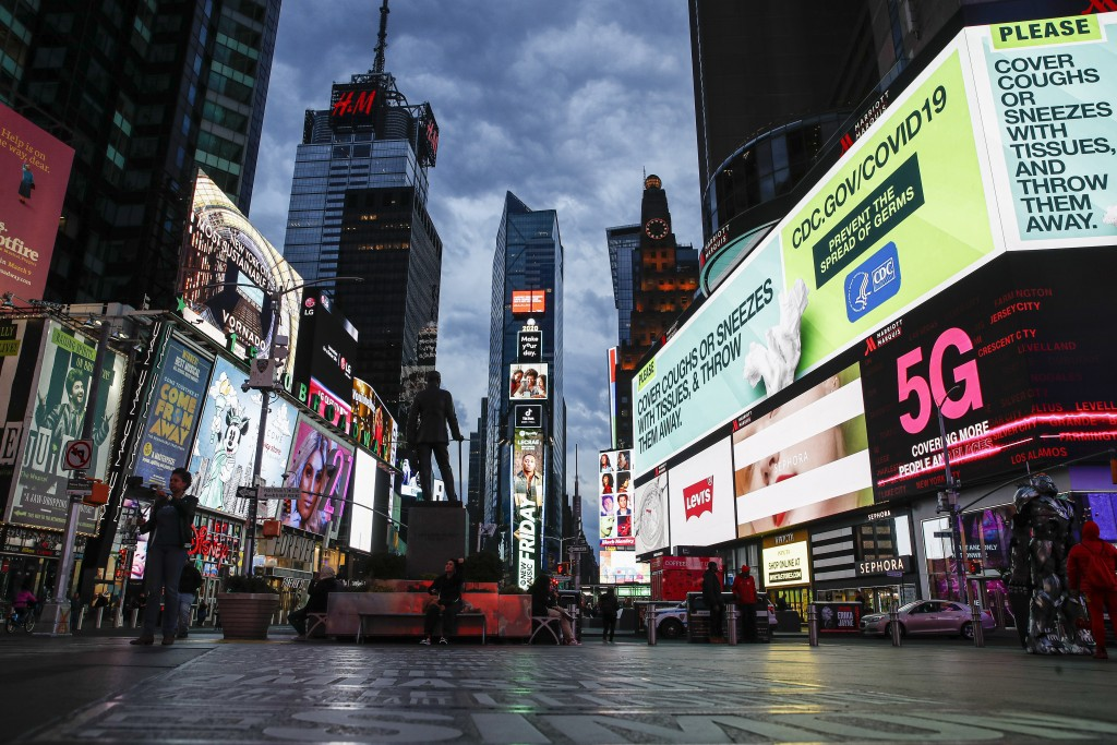 FILE - A screen displaying messages about COVID-19 light up a sparsely populated Times Square in New York on March 20, 2020. A new survey by The Actor...
