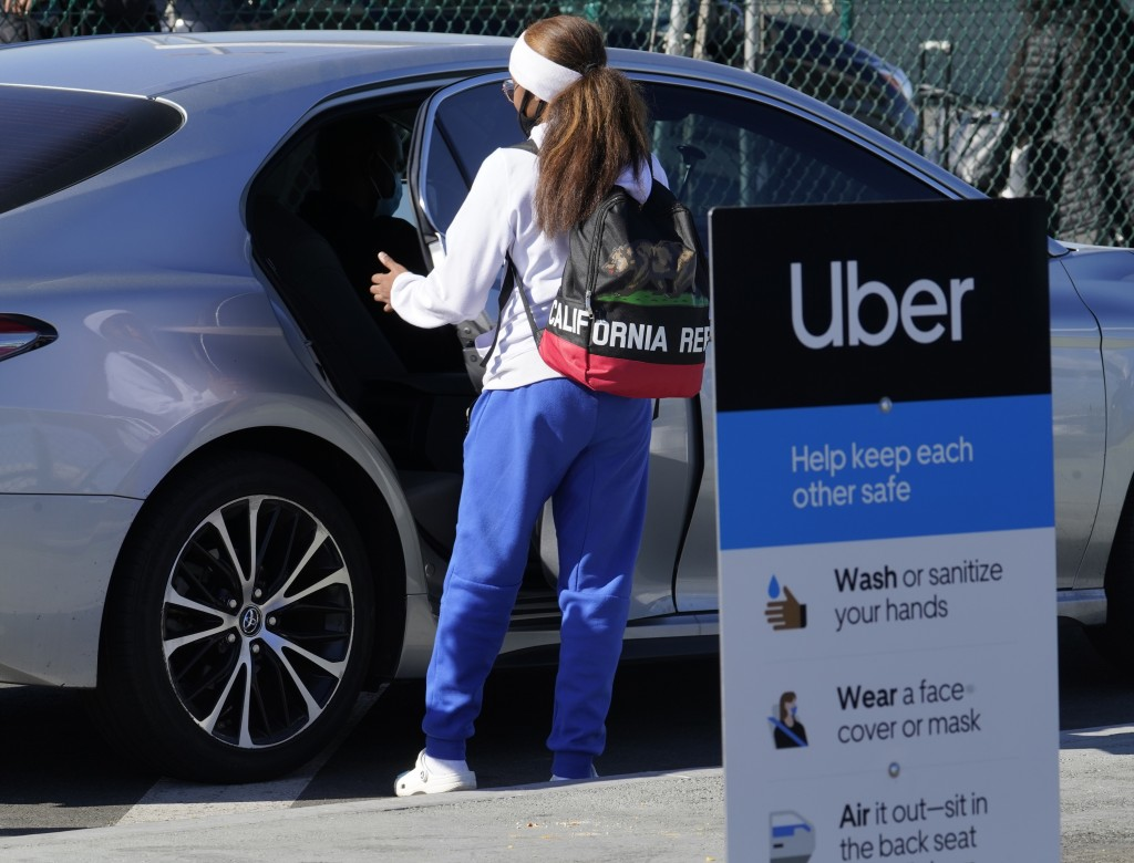 FILE - In this Nov. 13, 2020 file photo, a traveler rides in the back of an Uber vehicle at Los Angeles International Airport in Los Angeles.   Uber s...