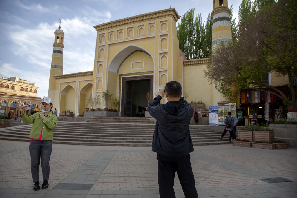 Visitors pose for photos outside the Id Kah Mosque in Kashgar in western China's Xinjiang Uyghur Autonomous Region, as seen during a government organi...
