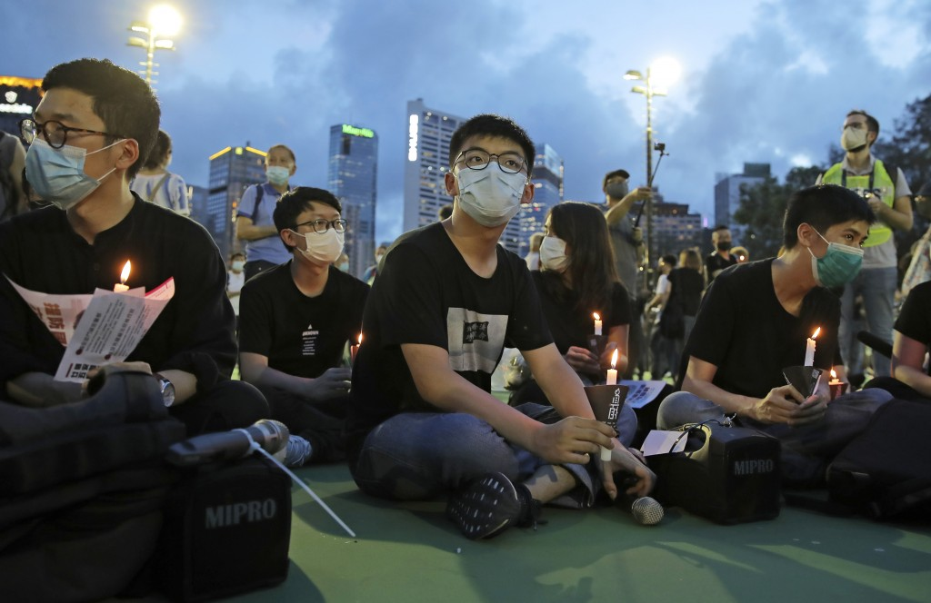 In this June 4, 2020, photo, democracy activist Joshua Wong, center, and Nathan Law, left, hold candles during a vigil to remember the victims of the ...