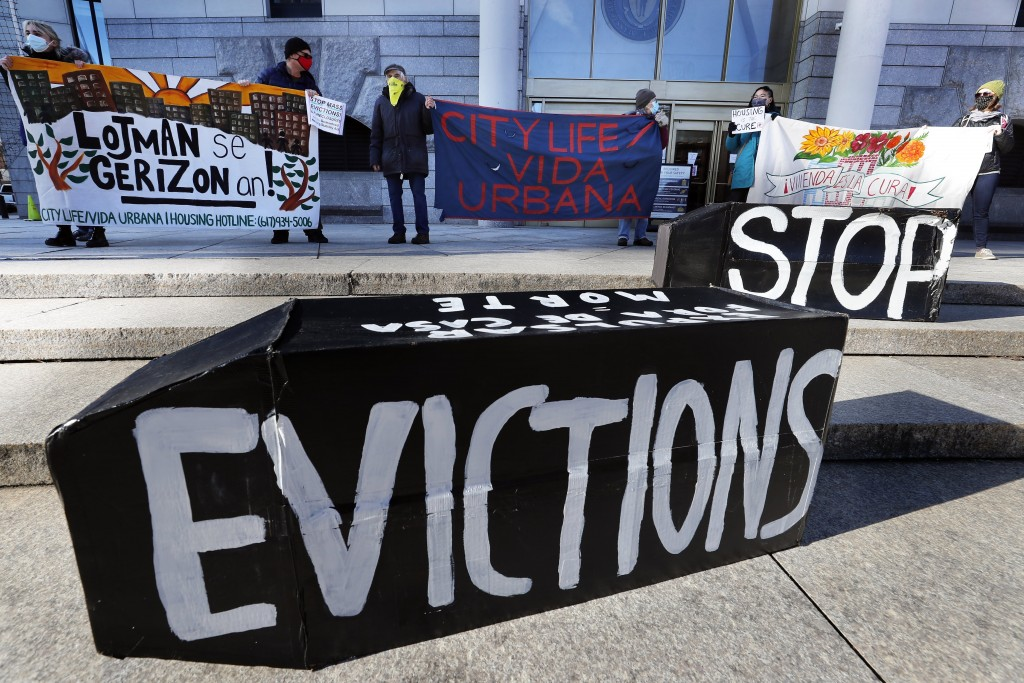 FILE - In this Jan. 13, 2021, file photo, demonstrators hold signs in front of the Edward W. Brooke Courthouse in Boston. A federal judge has ruled, W...