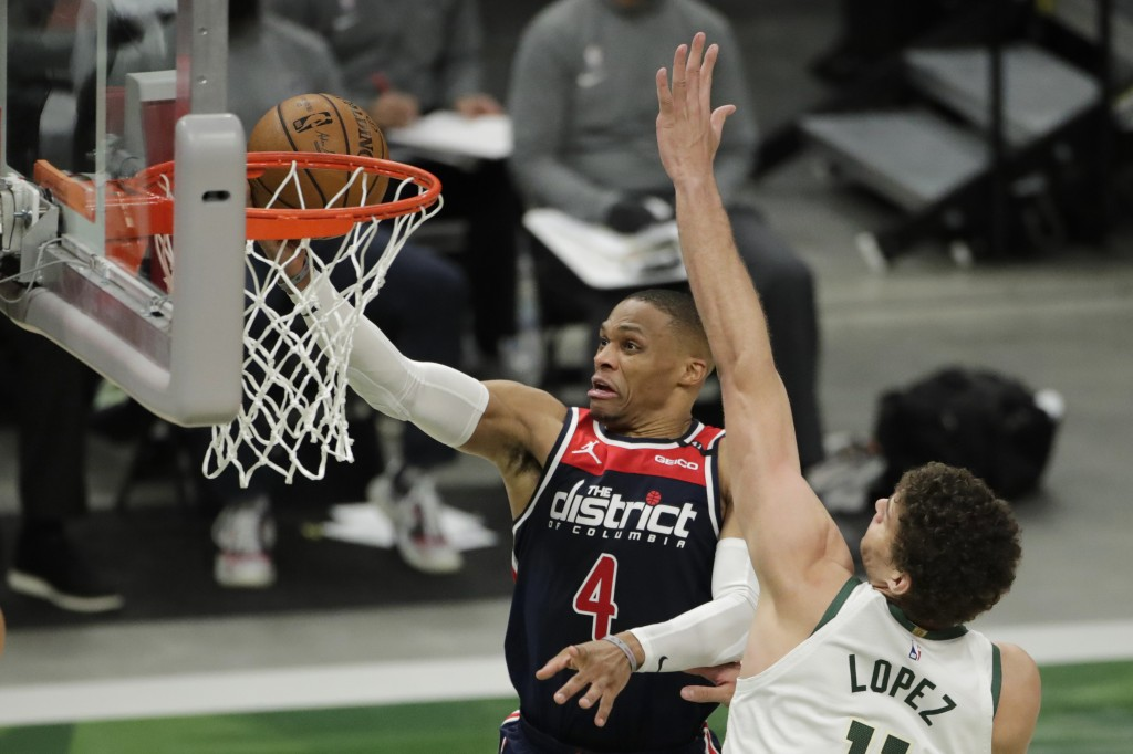 Washington Wizards' Russell Westbrook (4) goes to the hoop against Milwaukee Bucks' Brook Lopez during the first half of an NBA basketball game Wednes...