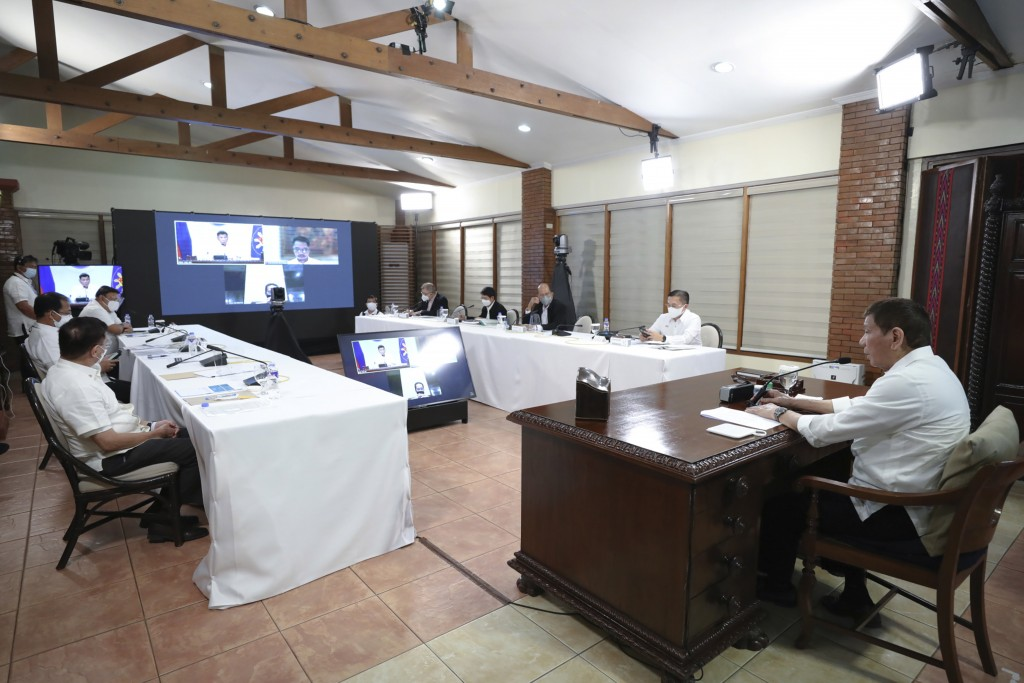 In this photo provided by the Malacanang Presidential Photographers Division, Philippine President Rodrigo Duterte, right, presides over a meeting wit...