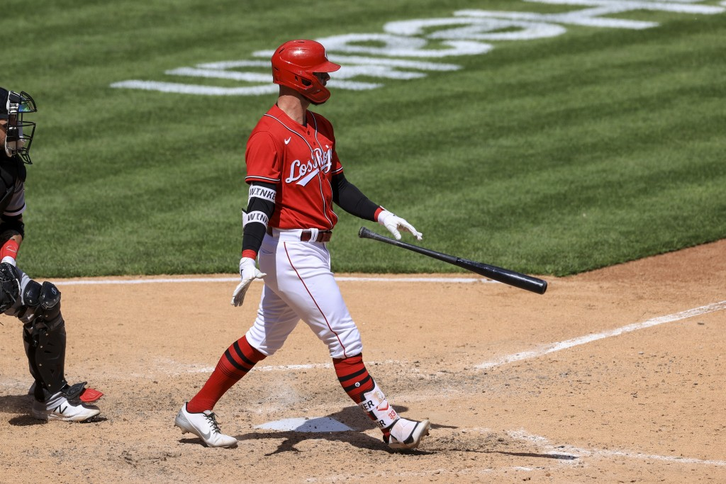 Cincinnati Reds' Jesse Winker throws his bat after hitting an RBI walk-off single during the tenth inning of a baseball game against the Chicago White...