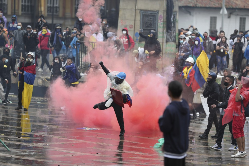 An anti-government protester returns a tear gas canister at the police during clashes in Bogota, Colombia, Wednesday, May 5, 2021. The protests that b...