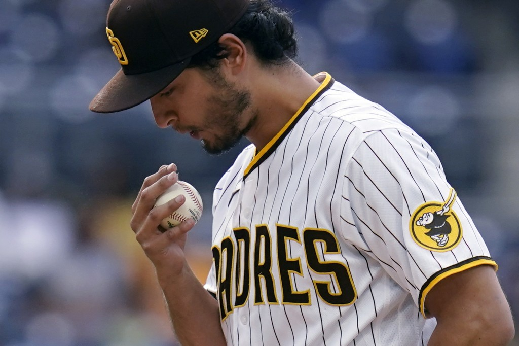 San Diego Padres starting pitcher Yu Darvish blows on his hand while warming up during the third inning of the team's baseball game against the Pittsb...