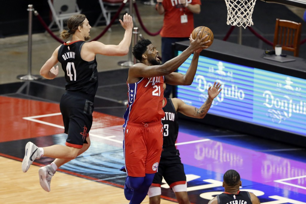 Philadelphia 76ers center Joel Embiid (21) gets a shot up past Houston Rockets forward Kelly Olynyk (41) and guard Kevin Porter Jr., right, during the...