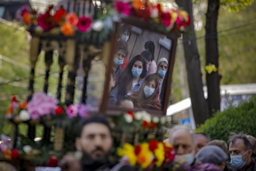 Members of the Armenian community in Romania, wearing face masks, are reflected in an icon as clergymen carry a structure symbolizing the tomb of Jesu...
