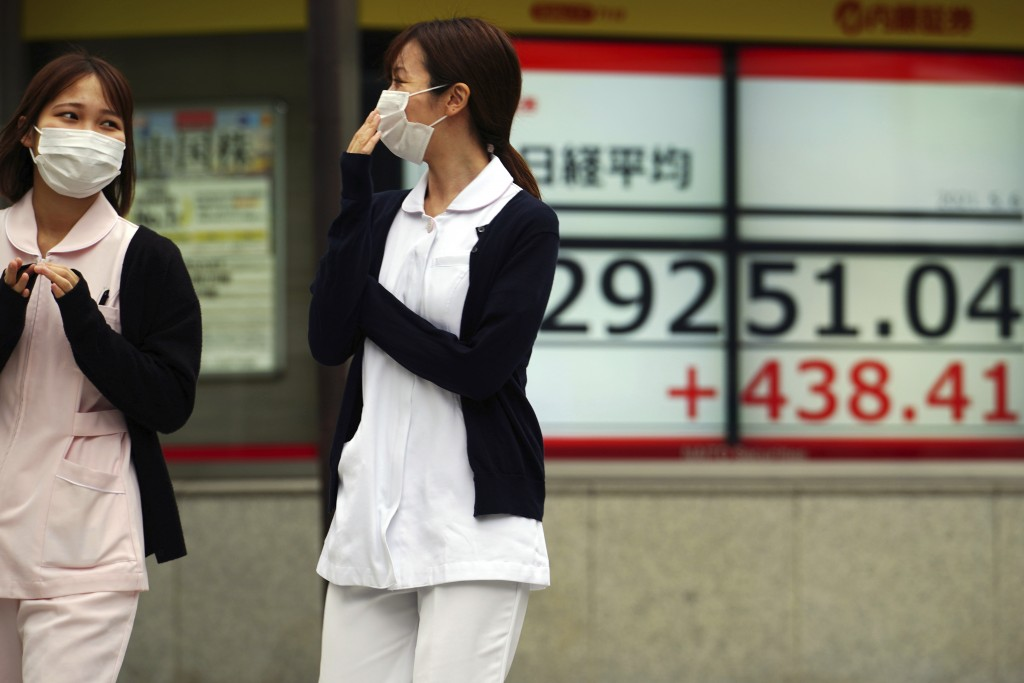 Women wearing protective masks walk in front of an electronic stock board showing Japan's Nikkei 225 index at a securities firm Thursday, May 6, 2021,...
