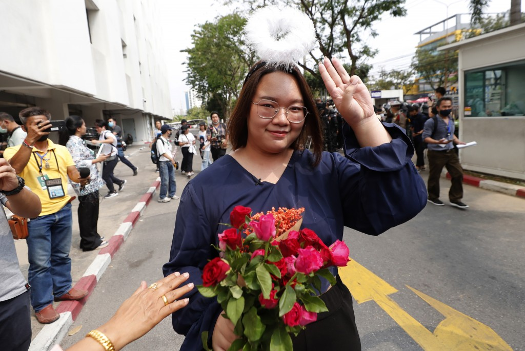 In this Monday, March 8, 2021, photo, pro-democracy activist Panusaya Sithijirawattanakul  gestures with a three-fingers salute, a symbol of resistanc...